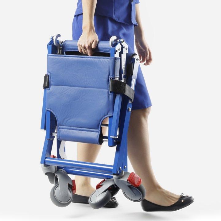 Stewardess carrying folded on-board wheelchair